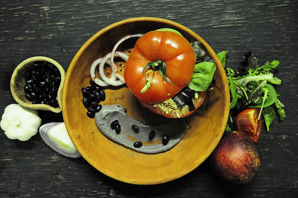Vegan Main: Beef Tomato stuffed with raw Ratatouille & Hickory, Tahini and Lime smoked Black Bean Hummus served with Almond Porcini Crumble (Image from The Bunyadi)